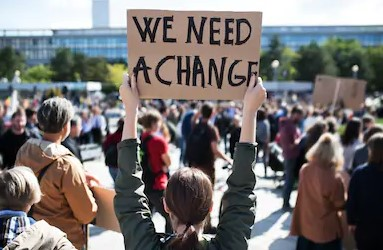 """A woman holds up a sign that says """"we need change"""""""